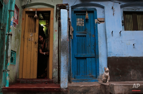 A Bangladeshi woman cleans the doorway to her home as a cat sits nearby early in the morning in Dhaka, Bangladesh, Thursday, Jan. 21, 2016. (AP Photo/A.M. Ahad)