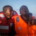In this Thursday, July 28, 2016 photo, Dustin, left, 11, from Nigeria, who said her mother died in Libya, cries next to her 10-year-old brother, as they aboard an overcrowded rubber boat and wait to be assisted by an NGO during a rescue operation on the Mediterranean Sea, about 23 kilometers (14 miles) north of Sabratha, Lybia. (AP Photo/Santi Palacios)