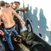 People kick and beat a Turkish soldier that participated in the attempted coup, on Istanbul's Bosporus Bridge, Saturday, July 16, 2016. Turkish President Recep Tayyip Erdogan told the nation Saturday that his government was working to crush a coup attempt after a night of explosions, air battles and gunfire across the capital that left dozens dead and scores wounded. Government officials said the coup appeared to have failed as Turks took to the streets overnight to confront troops attempting to take over the country. (AP Photo/Selcuk Samiloglu)
