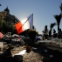 A French flag stands tall amongst a floral tribute for the victims killed during a deadly attack, on the famed Boulevard des Anglais in Nice, southern France, Sunday, July 17, 2016. French authorities detained two more people Sunday in the investigation into the Bastille Day truck attack on the Mediterranean city of Nice that killed at least 84 people, as authorities try to determine whether the slain attacker was a committed religious extremist or just a very angry man. (AP Photo/Laurent Cipriani)