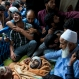 Kashmiri villagers grieve by the body of Burhan Wani, chief of operations of Indian Kashmir's largest rebel group Hizbul Mujahideen, during his funeral procession in Tral, some 38 Kilometers (24 miles) south of Srinagar, Indian controlled Kashmir, Saturday, July 9, 2016. Indian troops fired on protesters in Kashmir as tens of thousands of Kashmiris defied a curfew imposed in most parts of the troubled region Saturday and participated in the funeral of the top rebel commander killed by Indian government forces, officials and locals said. (AP Photo/Dar Yasin)