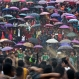 Indian Pnar or Jaintia tribesmen dance in muddy waters, as others hold umbrellas and watch Behdienkhlam festival celebrations in Tuber village, in the northeastern Indian state of Meghalaya, India, Thursday, July 21, 2016. Behdienkhlam is a traditional festival of the Pnars celebrated after sowing is done seeking a good harvest and to drive away plague and diseases. Young men symbolically drive away evil spirits by beating the roof of every house with bamboo poles. (AP Photo/Anupam Nath)