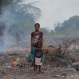 In this July 18, 2016, photo, a Sri Lankan woman and a child from a fishing family stand in the rising smoke from burning litter in a destroyed mangrove area in Kalpitiya, about 130 kilometers (81 miles) north of Colombo, Sri Lanka. Sri Lanka's government and environmentalists are working to protect tens of thousands of acres of mangrove forests _ the seawater-tolerant trees that help protect and build landmasses, better absorb carbon from the environment mitigating effects of global warming and reducing impact of natural disasters like tsunamis. Authorities have identified about 37,000 acres (15,000 hectares) of mangrove forests in Sri Lanka that are earmarked for preservation. (AP Photo/Eranga Jayawardena)