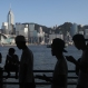 """A group of fans maneuver their smartphones as they play """"Pokemon Go"""" in Hong Kong, Monday, July 25, 2016. Pokemon fans participated in creatures hunting on Monday as the app was released to both iPhone and Android users. (AP Photo/Kin Cheung)"""