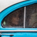 A woman looks out the window of an American classic car serving as a collective taxi during a rain shower in Havana, Cuba, Wednesday, July 27, 2016. Until the 1960 embargo, most new vehicles came to Cuba from the United States. Today most of Cuba's vintage American cars have been modified with newer engines, disc brakes and other parts, often scavenged from Soviet cars, and most bear the marks of decades of use. (AP Photo/Desmond Boylan)