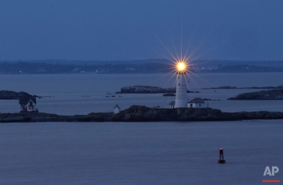In this Aug. 25, 2016 photo, Boston Light, America's oldest lighthouse, flashes in Boston Harbor as seen from Hull, Mass. (AP Photo/Elise Amendola)