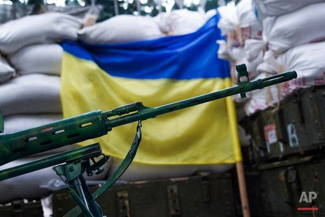 In this photo taken on Thursday, Aug. 25, 2016, a sniper rifle is placed in front of Ukrainian flag in the village of Marinka, near Donetsk, eastern Ukraine. (AP Photo/Max Black)