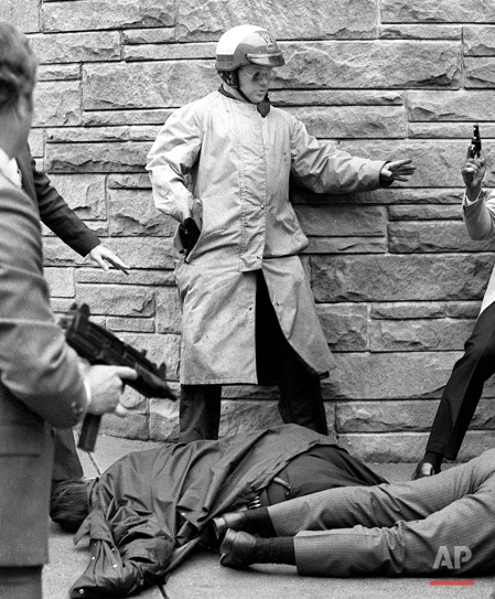 Officers with guns drawn rush towards assassin John Hinckley, not shown, after he fired his weapon hitting President Ronald Reagan, Officer Delahanty, and Secret Service Agent Tim McCarthy after a Washington hotel, D.C., March 30, 1981. (AP Photo/Ron Edmonds)