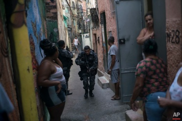"""In this June 29, 2016 photo, a police officer patrols among residents during an operation against drug traffickers at the """"pacified"""" Jacarezinho slum in Rio de Janeiro, Brazil. The Pacification Police Units, known by the Portuguese acronym UPP, were created in 2008, setting up community stations in at-risk areas, mostly near sports venues, posh tourist districts and downtown. A drug gang leader called the program a """"facade."""" He said that drug dealers were initially worried and kept a low profile, but soon it was back to business as usual. (AP Photo/Felipe Dana)"""