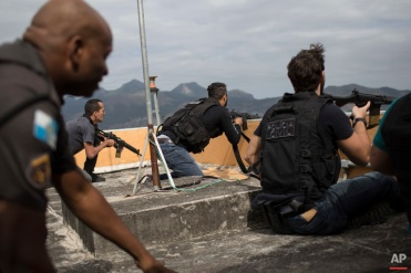 """In this July 7, 2016 photo, police exchange gunfire with drug traffickers at the """"pacified"""" Alemao slum complex in Rio de Janeiro, Brazil. Half a dozen officers had entrenched themselves behind a cable car station while they shot it out with suspected drug traffickers in the sprawling cluster of slums in north Rio. Shootouts erupt daily, even in slums where community policing programs had successfully rewritten the narrative in recent years. (AP Photo/Felipe Dana)"""