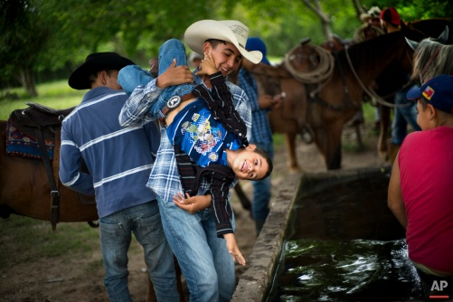 In this July 29, 2016 photo, a cowboy playfully threatens to dunk a younger boy into a water troff, during an improvised rodeo event at a farm in Sancti Spiritus, central Cuba. In the flat grasslands in the central province of Sancti Spiritus, a group of neighboring cattle ranchers founded a non-governmental organization called Future Ranchers more than a decade ago to revive Cuba's rodeo culture, which dates back centuries to Spanish colonial times. (AP Photo/Ramon Espinosa)
